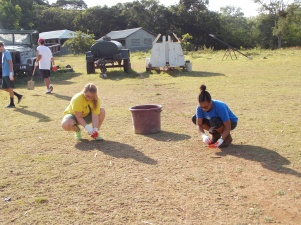 Our students picking up various trash, debris, rocks, glass, etc from the area the kids play soccer. Preparing for us to build a soccer field.