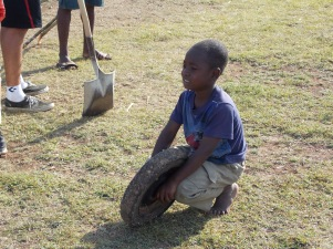 One of the orphan boys playing with a tire off a wheel barrel