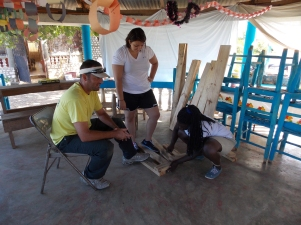 One of our leaders showing two of our students what to do next in the building of their table bench